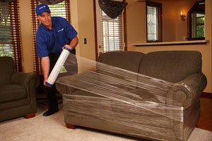 Nilson Van United Mover is Wrapping a Couch in Preparation to Moving It